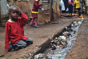 A_young_boy_sits_over_an_open_sewer_in_the_Kibera_slum,_Nairobi